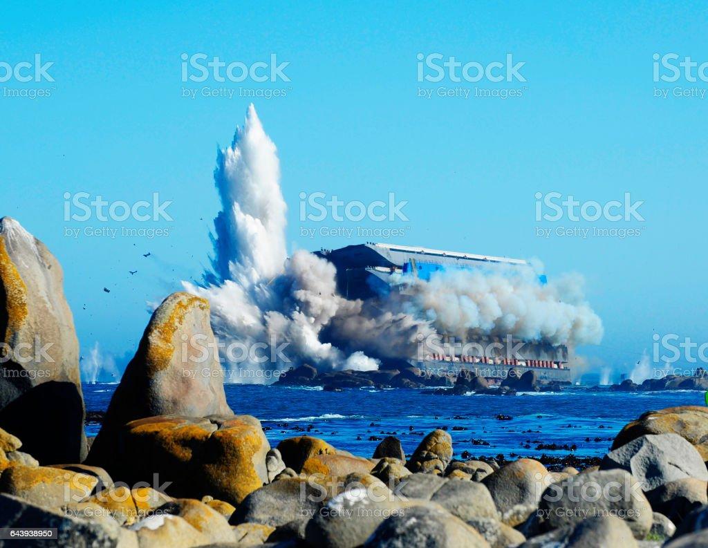 Beached ship explodes at sea stock photo