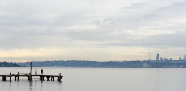 Beachgoers at Kirkland  Marina pier looking at Seattle skyline across lake Washington stock photo