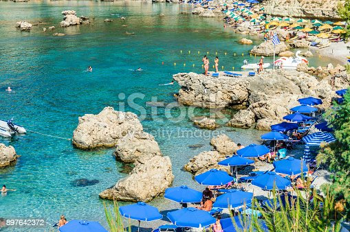 Beachgoers enjoy famous Anthony Quinn Bay beach in Rhodes, Greece