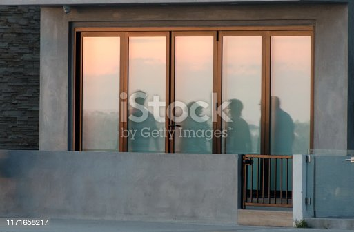 Beachgoers reflections at windows of a  beach house brightly lid by sunset, Newport Beach, Southern California
