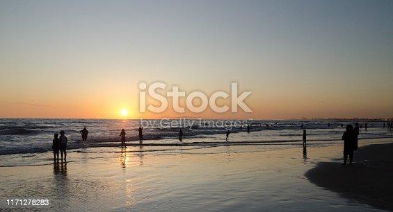 Beachgoers watching sunset at Newport Pier, Southern California