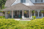 """""""Shingle Style Beachside Cottage. Patio chairs,wicker furniture and hanging flower baskets.  Juniper hedge in front."""""""