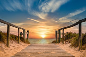 Beachside pathway leading to the ocean with spectacular sunrise in Tannum Sands, QLD, Australia