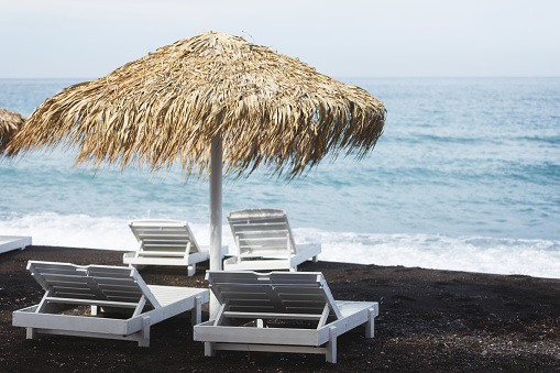 Beachside thatched umbrella and beach beds with a sea view, Santorini island, Greece