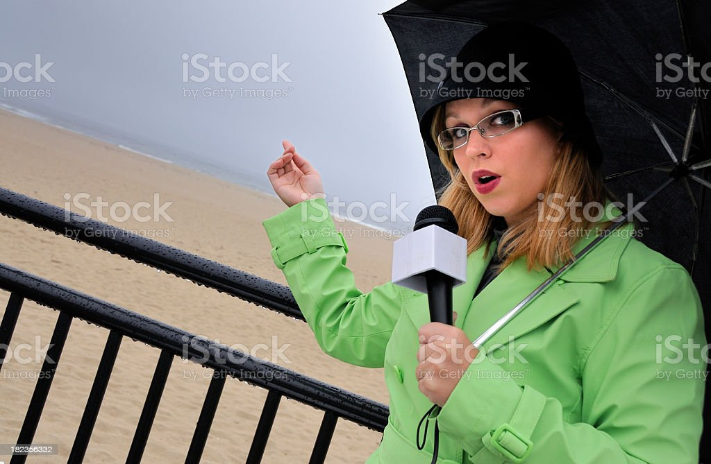 Beachside Weathergirl Pointing to Approaching Storm stock photo
