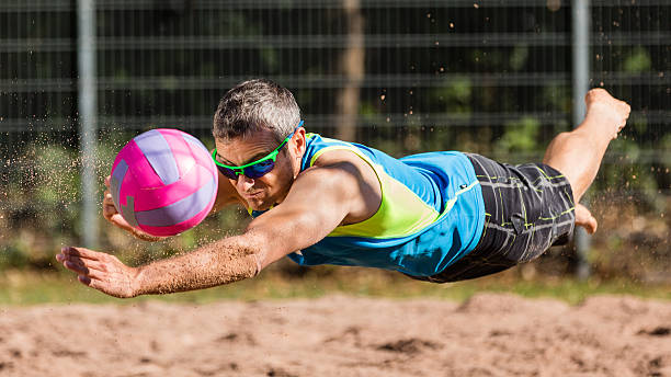 Beachvolleyballer flying stock photo