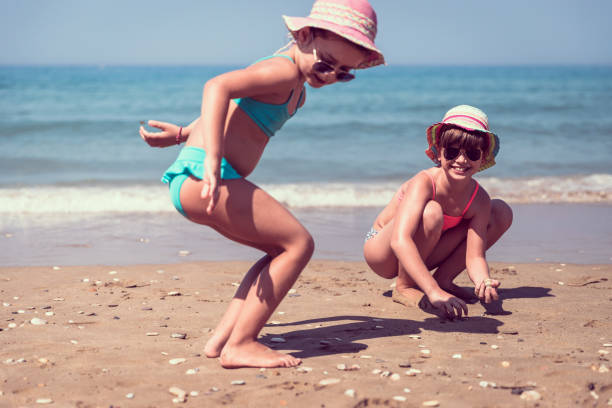 beachy days were made for play - little girl picking up sea shells at the beach stock pictures, royalty-free photos & images
