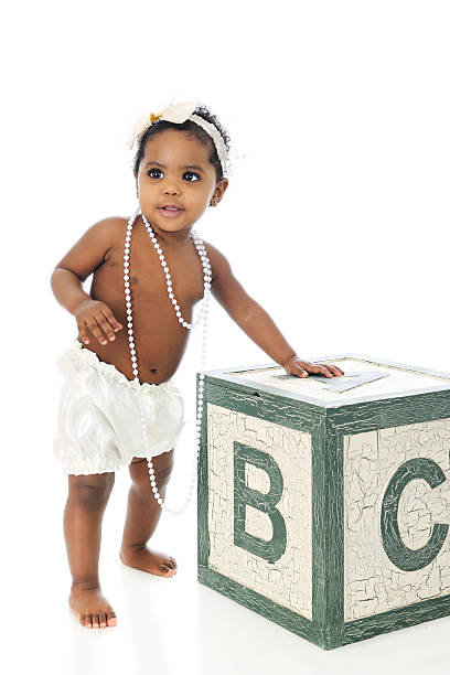 Beaded Baby A beautiful baby girl standing with support.  She wears a white hair bow, long strands of beads and silky bloomers.  On a white background. little girls in panties stock pictures, royalty-free photos & images
