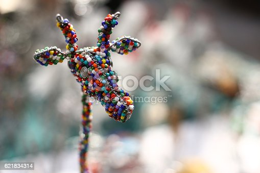 A handmade giraffe souvenir constructed with wire and beads is seen on a market stall in a South African handmade arts and crafts market