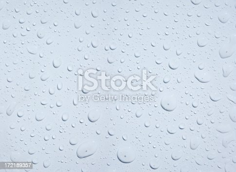 Water drops beaded up on a clean white surface.