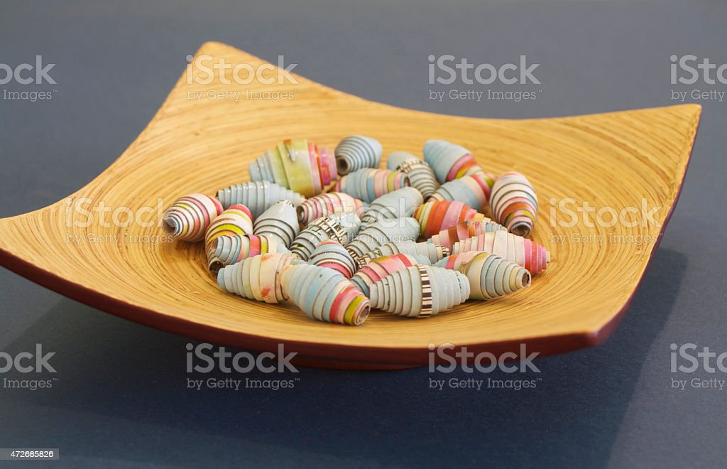 Beads made from Rolled Cardboard on a Bamboo Plate stock photo