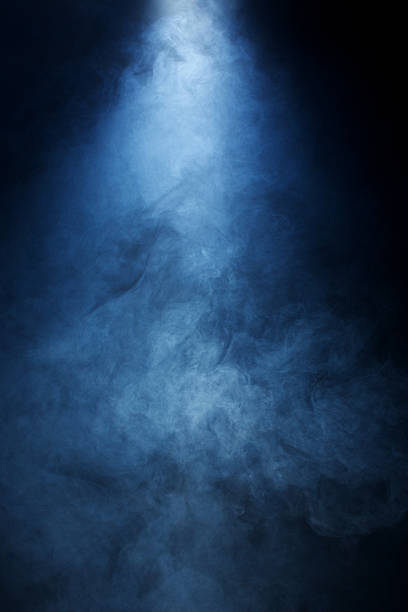 Beam of Light Passing Through Blue Smoke onBlack Background Narrow beam of light passing through blue/grey smoke on a black background. Great used as a dramatic overlay texture or background. smoke physical structure stock pictures, royalty-free photos & images