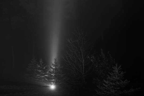 Beam of light shooting to the sky in the foggy night - black and white – zdjęcie