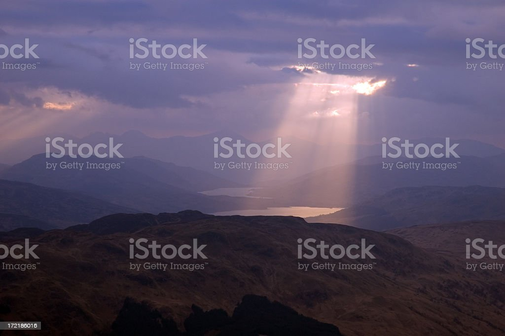 A beam of sunlight penetrating gray clouds stock photo