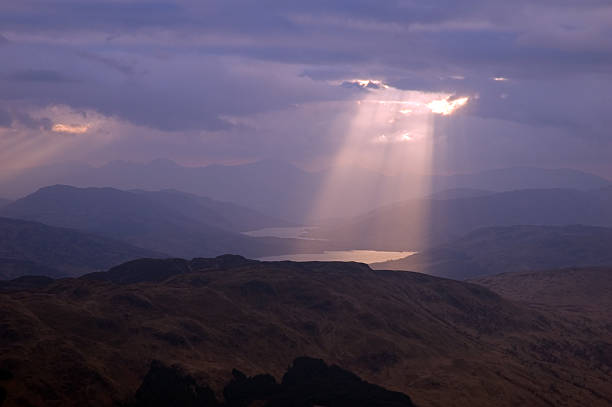 A beam of sunlight penetrating gray clouds A beam of sunlight breaks through the clouds and lights the surface of a loch in the Highlands of Scotland. emergence stock pictures, royalty-free photos & images
