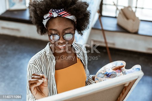Nice makeup. Beaming African-American creative artist with nice makeup smiling while painting