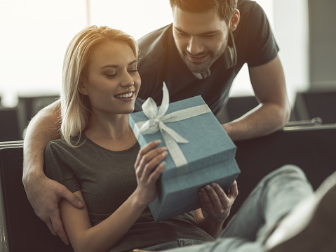 Happy birthday my dear. Outgoing man giving gift for smiling woman. She opening it. Happy lovers concept