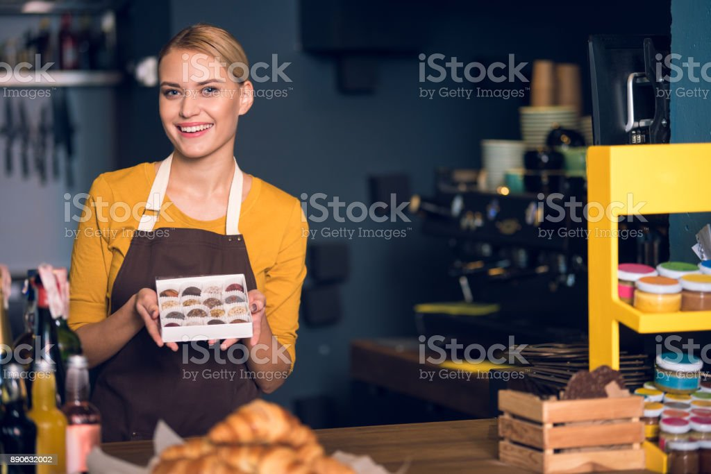 Beaming female pastry chef keeping sweets stock photo