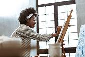 istock Beaming international art student sitting near window and painting 1140711061