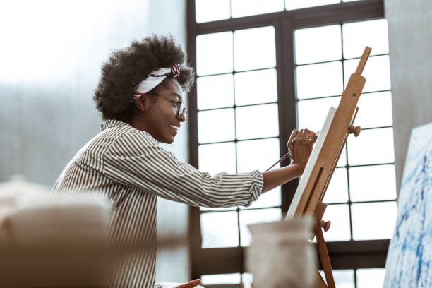 Beaming international art student sitting near window and painting Beaming student. Beaming international art student sitting near window and painting on canvas hobbies stock pictures, royalty-free photos & images