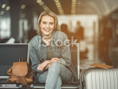 Portrait of laughing woman sitting on chair near baggage in airport. Glad tourist waiting for journey concept