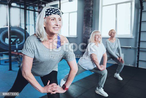 936573360 istock photo Beaming senior lady taking group training at gym 936573330