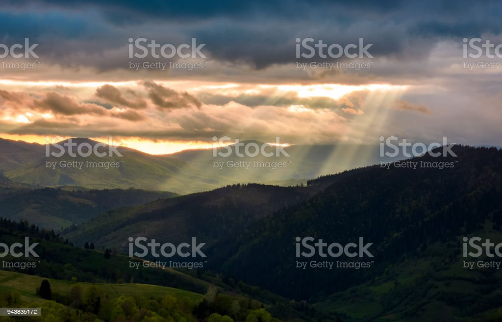 beams of light over the mountains stock photo