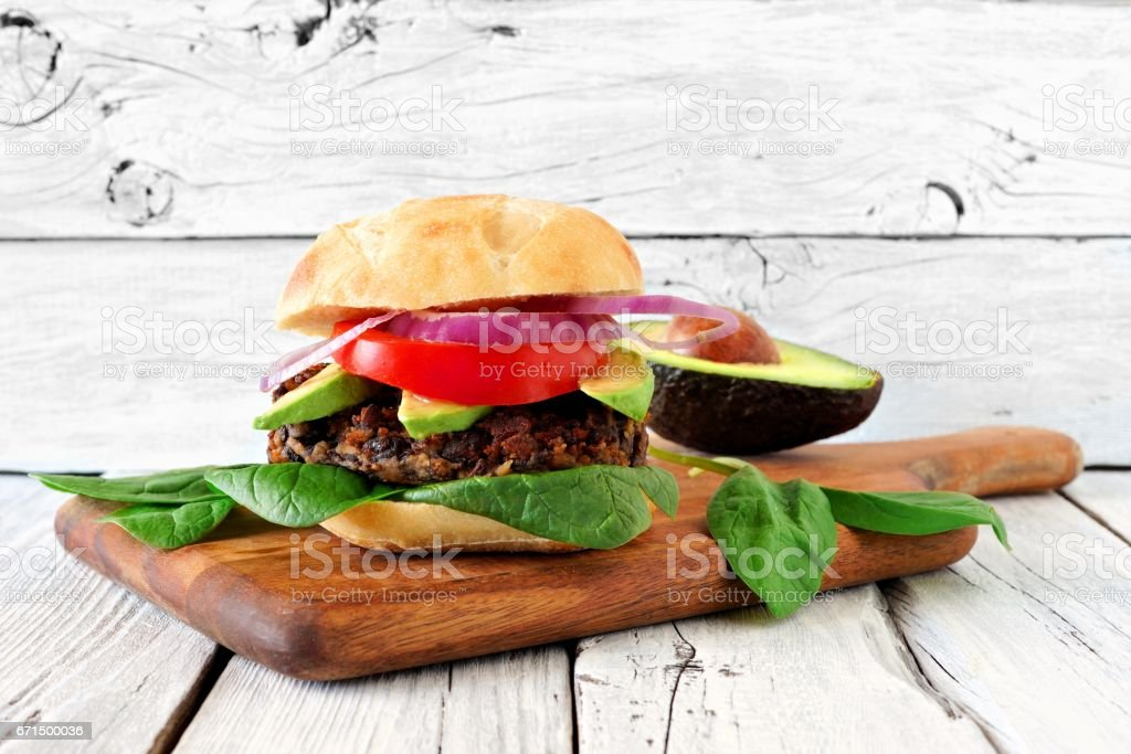Bean and sweet potato veggie burger against rustic white wood stock photo