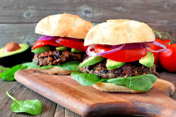 Bean and sweet potato veggie burgers over a wood background stock photo