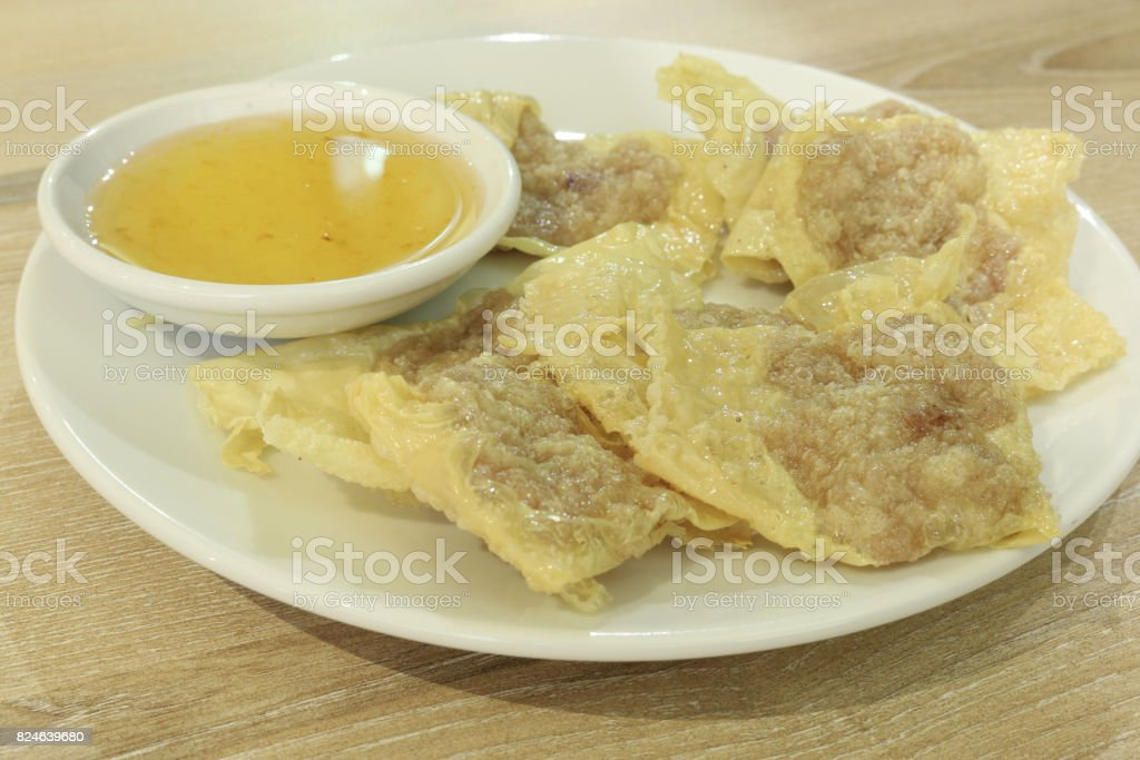 bean curd skin pork roll with plum sauce on white dish and wood table stock photo