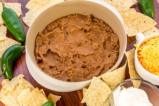 bean dip with jalapenos, sour cream and cheddar cheese stock photo
