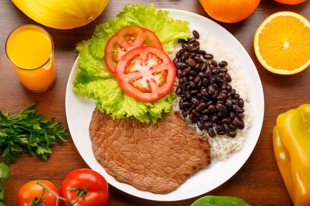 ahşap arka planda salata ile fasulye, pirinç ve biftek - fasulye stok fotoğraflar ve resimler