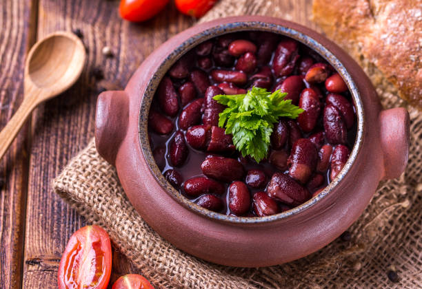 Bean soup in home crafted bowl with tomatoes on wooden table. stock photo