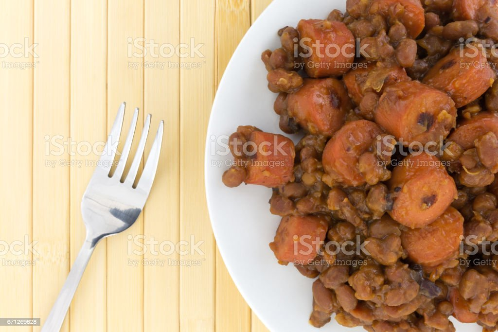 Beans and hot dogs on a plate with a fork stock photo