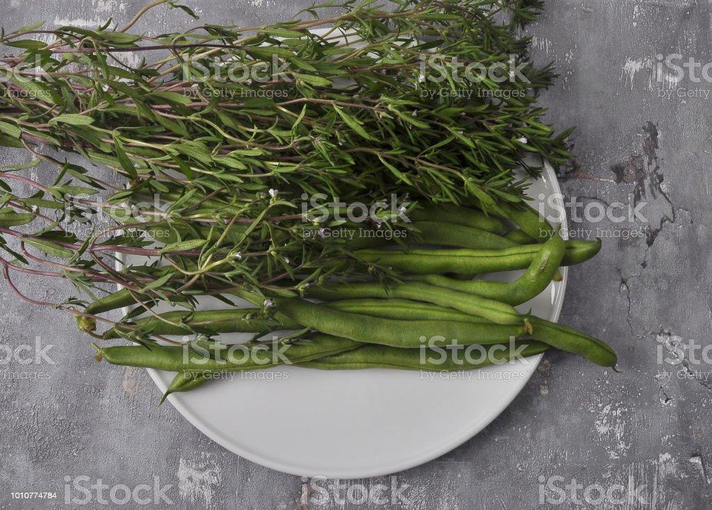 Bohnen und Bohnenkraut auf Platte und Beton – Foto