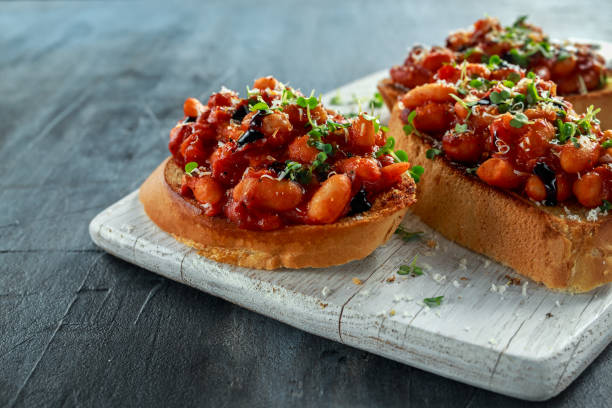 Beans fried in tomato sauce on toasted bread with cross salad sprinkle stock photo