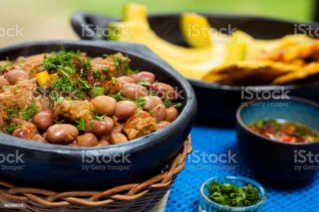 Beans with pork meat served with avocado and patacon stock photo