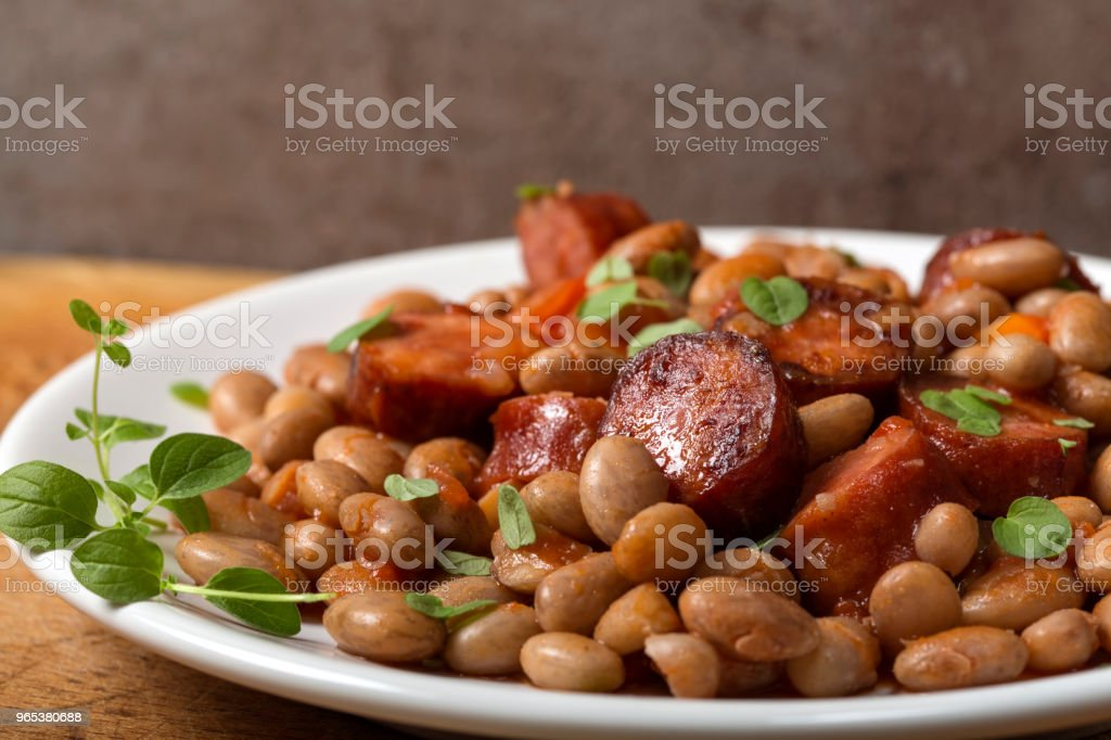 Beans with smoked pork sausages on plate and tomato sauce with green herbs royalty-free stock photo
