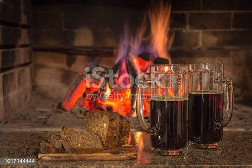 istock Bear in two glasses, sliced bread on a background of live fire. 1017144444