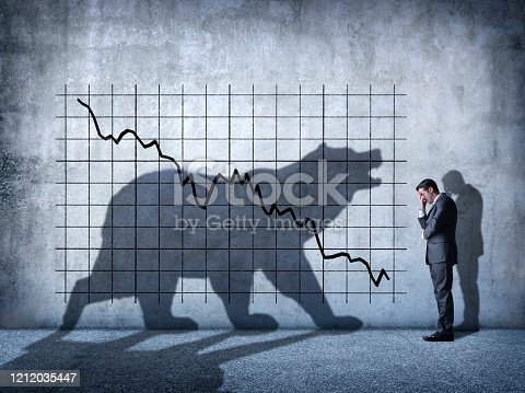 A businessman covers his eyes as he can't watch a descending stock chart and an ominous shadow of a bear that is cast on the wall above him.