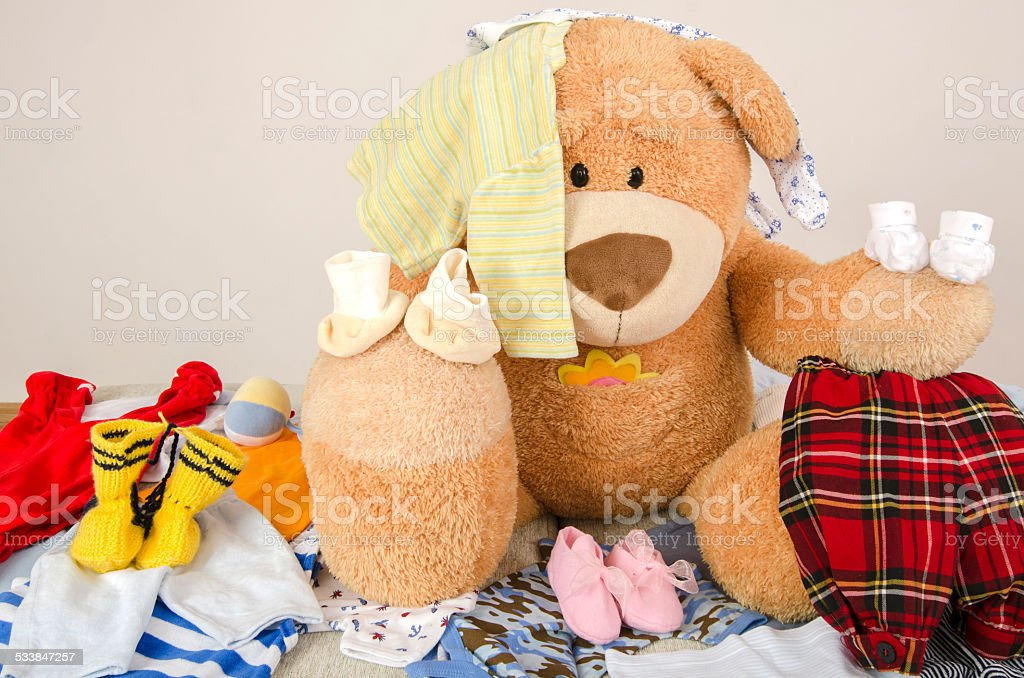 Bear toy on a bed with different colorful new born clothes.Colorful...