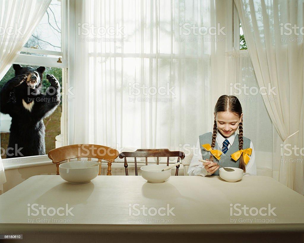 Bear watching girl eating stock photo