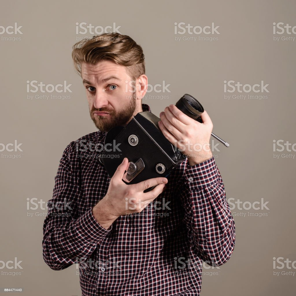 beard man in a checkered shirt holds in the hands of an old movie camera stock photo