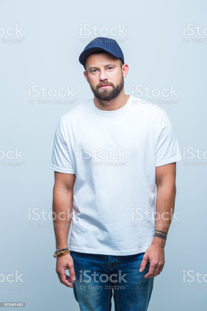Beard man looking serious Portrait of a beard man wearing cap looking at camera with serious expression on white background Adult Stock Photo