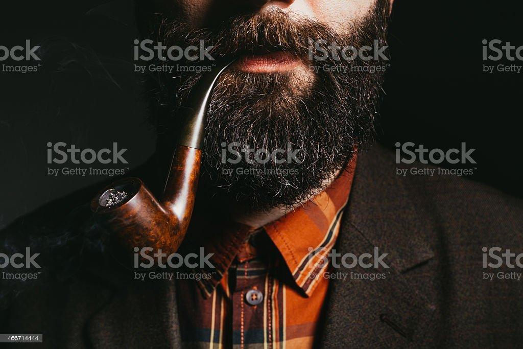 Beard man smoking tobacco pipe stock photo