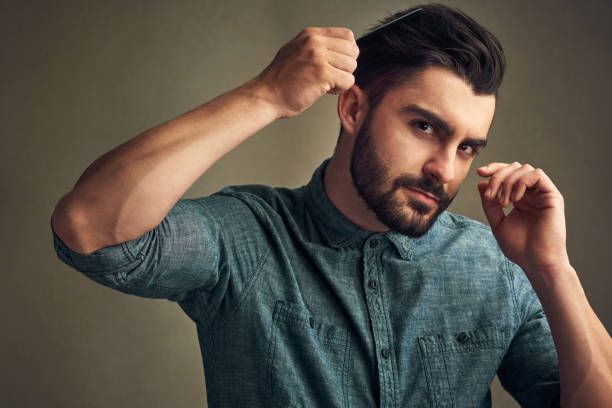 Beard season is here Studio shot of a handsome young man combing his hair against a grey background combing stock pictures, royalty-free photos & images