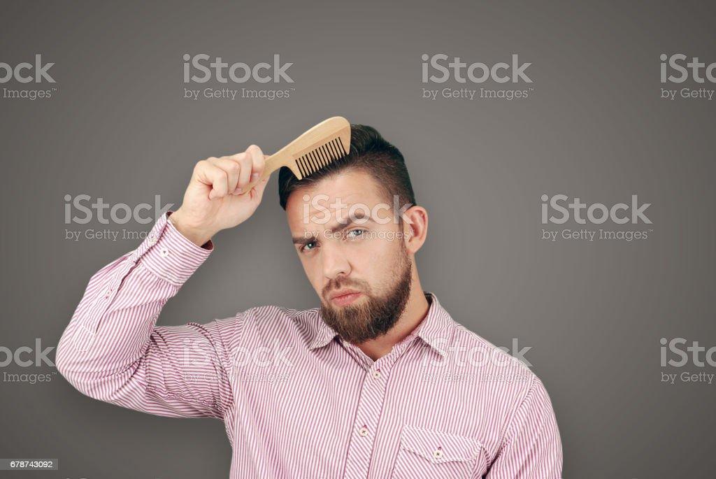 Homme adulte barbu avec un peigne en bois photo libre de droits