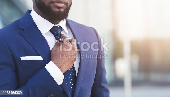 973213156istockphoto Bearded Afro Businessman Adjusting Tie In Urban Area, Cropped 1173565309