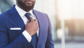 Unrecognizable Bearded Afro Businessman Adjusting Tie Standing In Urban Area. Free Space, Cropped