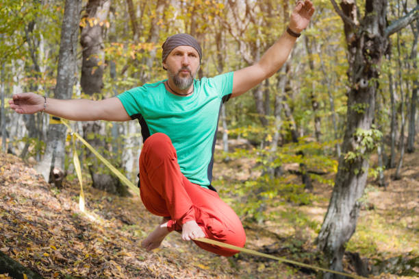 A bearded aged man sits on a slackline balancing in meditation. Professional tightrope walker in the autumn forest stock photo